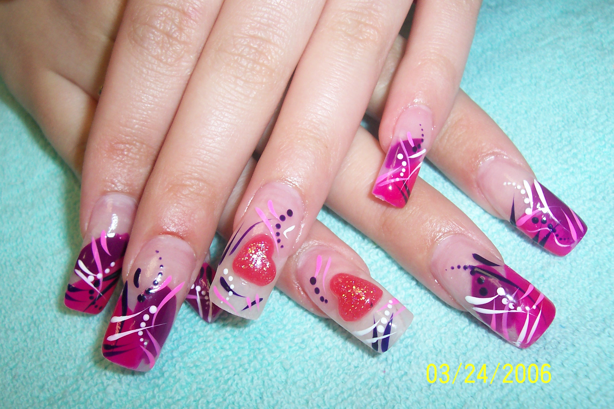 The hearts in these nails are formed using red acrylic. The red hearts ...